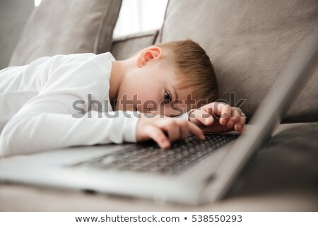 Little alone sad boy lies on sofa while using laptop Stock photo © deandrobot