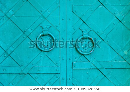 Old rusty metal door knocker on an old wooden entrance door Stock photo © smuki