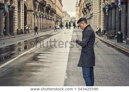 Vertical image of calm young man smoking cigarette Stock photo © deandrobot