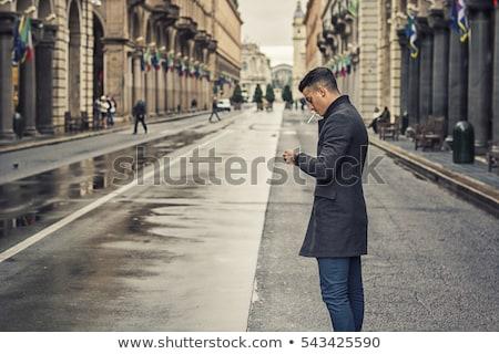 vertical image of calm young man smoking cigarette stock photo © deandrobot