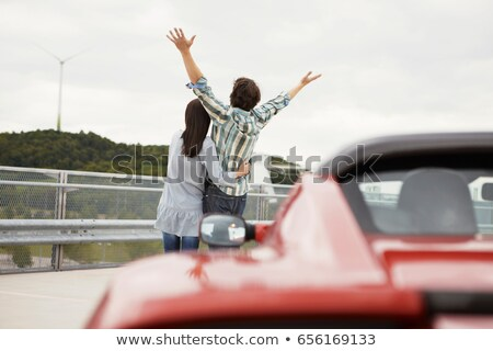 couple close together near electric car stock photo © is2