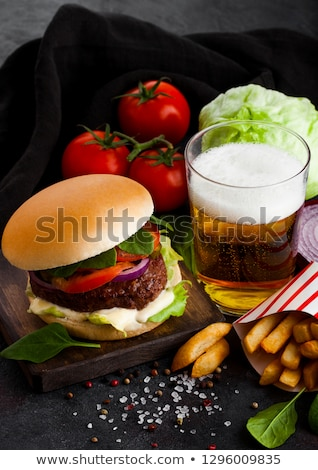 fresh beef burger with sauce and vegetables and glass of craft lager beer with potato chips fries on stock photo © denismart