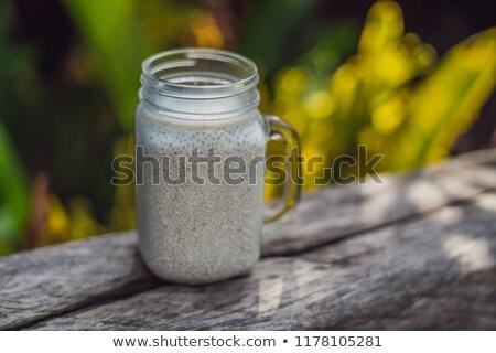 Healthy layered dessert with chia pudding in a mason jar on rustic background Stock photo © galitskaya