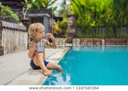 The boy eats chia pudding in the morning by the pool. Healthy breakfast. Useful food for children Stock photo © galitskaya