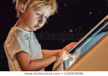 The boy uses the touch screen in the dark ストックフォト © galitskaya