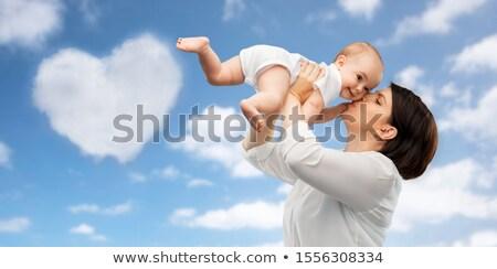 mother kissing baby over sky background Stock photo © dolgachov