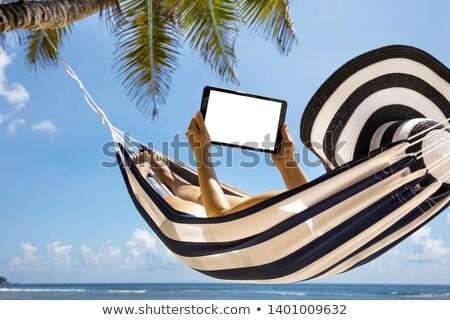 woman lying on striped hammock using digital tablet stock photo © andreypopov