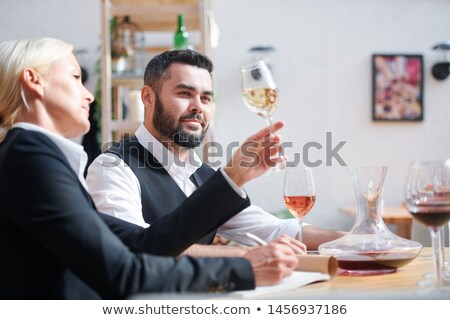 Young successful cavist looking at white wine held by his colleague Stock photo © pressmaster