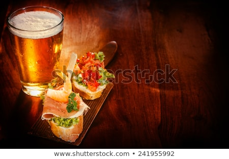 Frothy Alcohol Beverage in Glass and Tasty Snack Stock photo © robuart