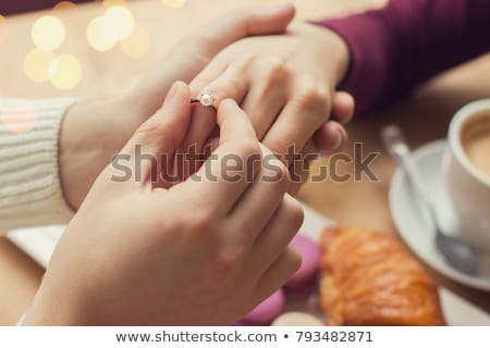 man puts engagement ring on womans finger Stock photo © dolgachov
