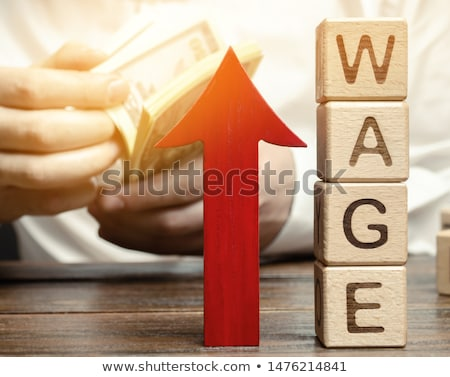 Person's Hand Holding Growth Arrow Near Wage Stock photo © AndreyPopov