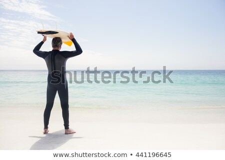 Rear view of senior male surfer carrying the surfboard on his head at beach Stock photo © wavebreak_media