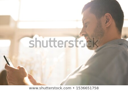 Young serious businessman with smartphone scrolling through information Stock photo © pressmaster