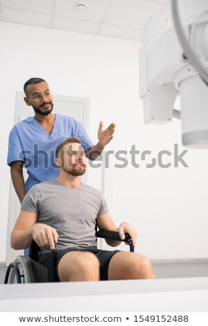 Doctor in blue uniform showing patient on wheelchair new medical equipment Stock photo © pressmaster