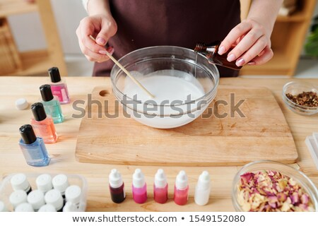 young woman pouring essential oil from small bottle into liquid soap mass stock photo © pressmaster