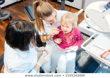 Woman dentist looking after baby teeth of a little girl Stock photo © Kzenon