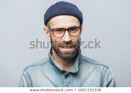 Indoor shot of handsome unshaven male with satisfied expression, rejoices achieving success at work, Stock photo © vkstudio