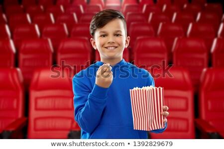 boy with paper bucket of popcorn at movie theater Stock photo © dolgachov