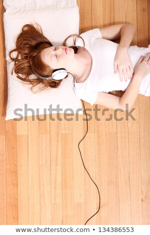 young redhead woman is daydreaming while listening to music with headphones Stock photo © Rob_Stark