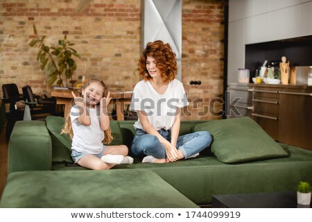 Beautiful red-haired woman posing while sitting on a sofa in the living room Stock photo © wavebreak_media