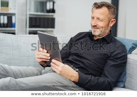 Businessman smiling as he reads a tablet-pc Stock photo © stryjek