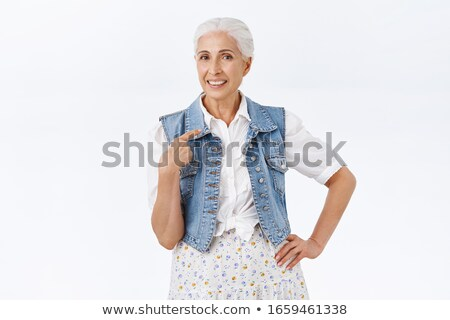 Mature woman standing with hand on hip and pointing herself Stock photo © bmonteny
