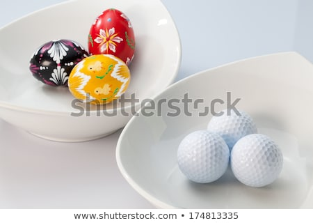 two white ceramics bowls with golf balls on the glass table stock photo © capturelight
