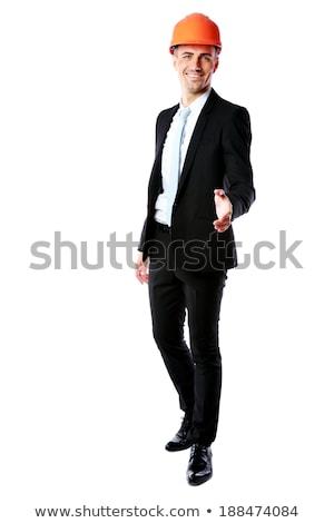 full length portrait of a businessman in helmet offering handshake over white background stock photo © deandrobot