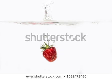 fresh strawberries falling into water with splashes stock photo © zerbor