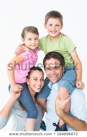 Happy two parent giving their children a piggy back Stock photo © wavebreak_media