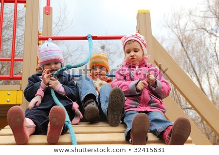 three children sit on artificial hill on playground stock photo © paha_l