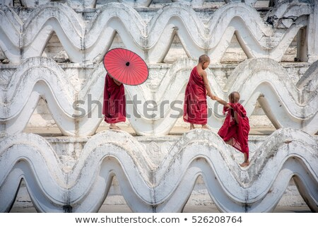 Buddhist novice monk climbing temple Stock photo © szefei