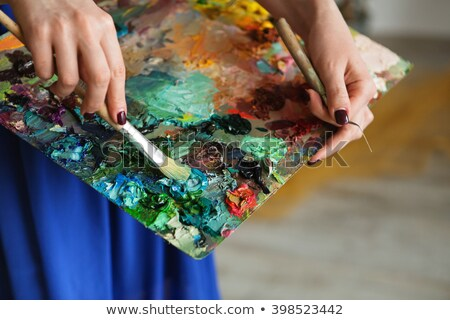 Paintbrush in woman hands mixing paints on palette Stock photo © deandrobot