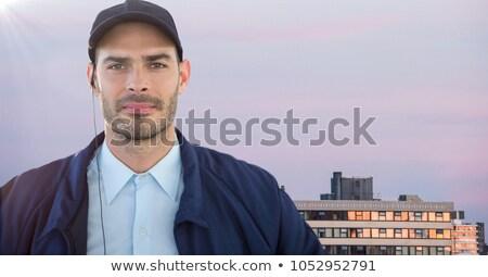 Confident Security Guard Listening To Earpiece Against Building Stock photo © AndreyPopov