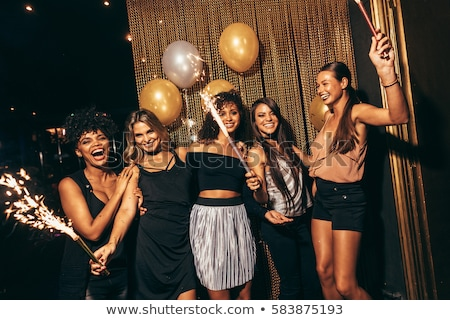 happy young women with sparklers at night club Stock photo © dolgachov