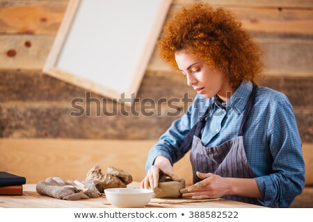 Creative young woman potter making earthen dishes in workshop Stock photo © deandrobot