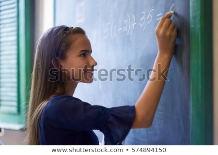 Stock photo: Girl Doing Math Exercise At Blackboard In High School Class