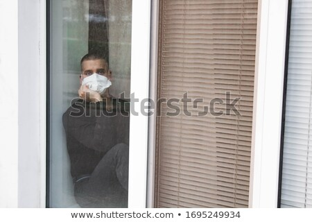 Man sitting, hands together, at window Stock photo © IS2