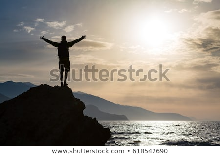 Man with arms outstretched celebrate mountains sunrise stock photo © blasbike