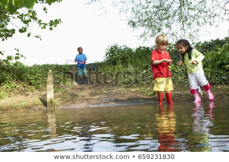 Children in rainboots playing in pond Stock photo © IS2