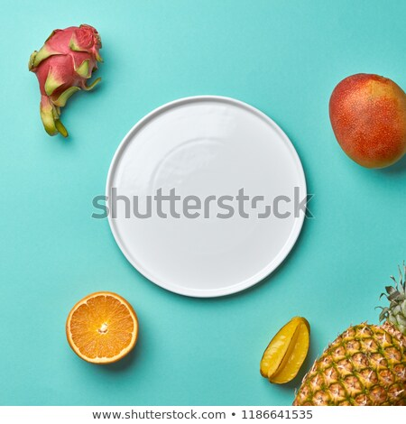Different tropical fruits and empty white plate on a blue background with copy space. Flat lay Stock photo © artjazz