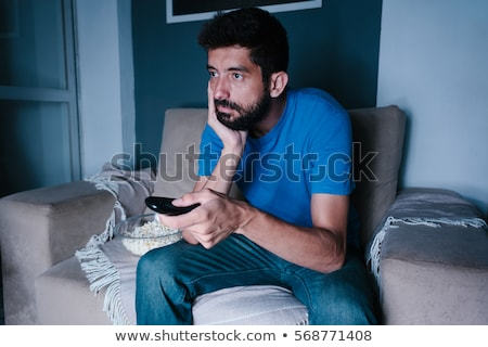 bored man with remote and popcorn stock photo © ichiosea