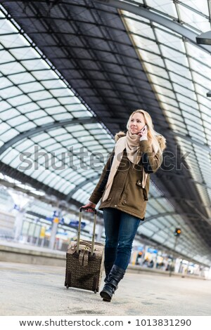 Woman with her luggage walking along the platform in train station Stock photo © Kzenon