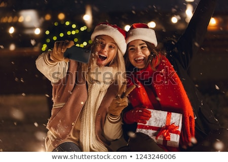 happy young friends sitting outdoors in evening in christmas hats holding gift box take a selfie by stock photo © deandrobot