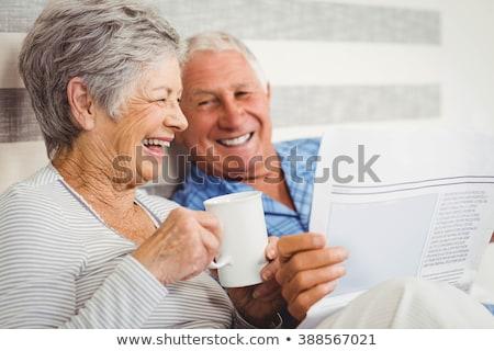 senior woman with coffee reading newspaper at home Stock photo © dolgachov