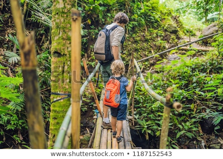 Stock photo: Father and son travelers on the suspension bridge in Bali. Traveling with children concept.