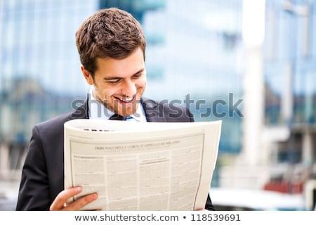 Smiling businessman reading newspaper Stock photo © deandrobot