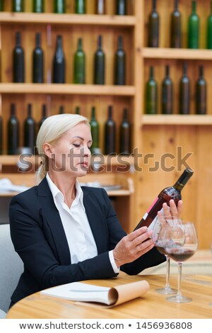 Mature confident winery expert with bottle of wine working in cellar Stock photo © pressmaster