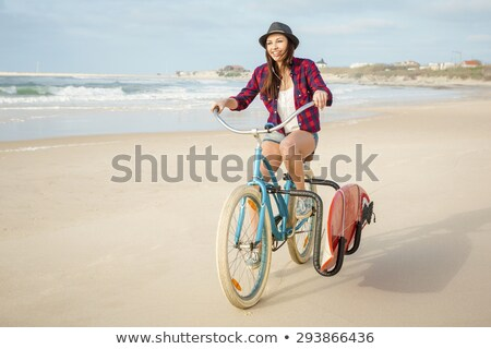 surfer girl riding a bicyicle stock photo © iko