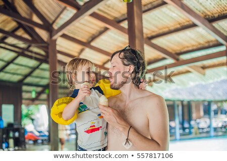 father and son eating ice cream in aquapark under a thatched roof stock photo © galitskaya